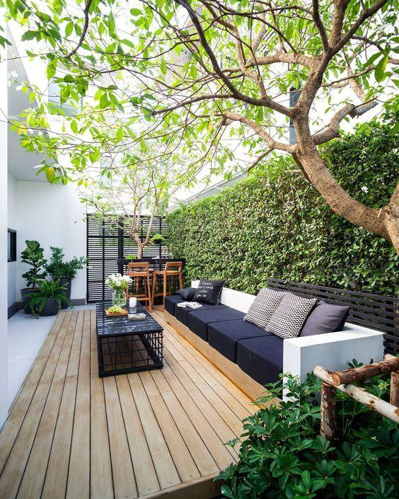 Backyard with wooden deck creating seating area with sofa and coffee table.