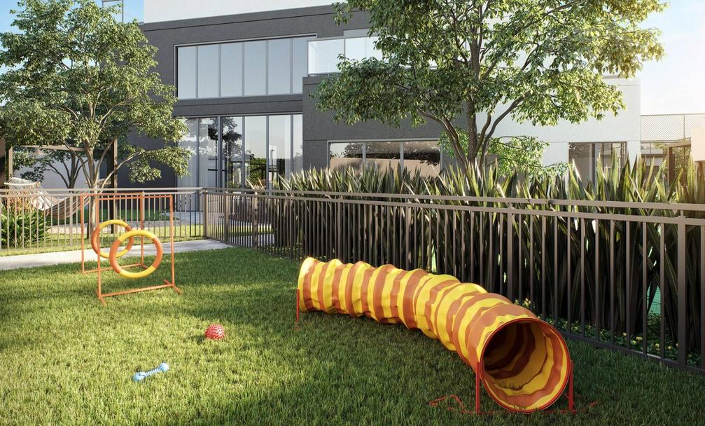 Grassy pet place with tunnel and jumping equipment, fenced with metal closure.