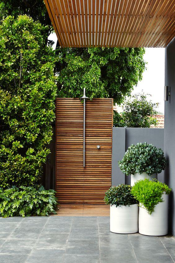 Outdoor shower with vegetation in its wrap.