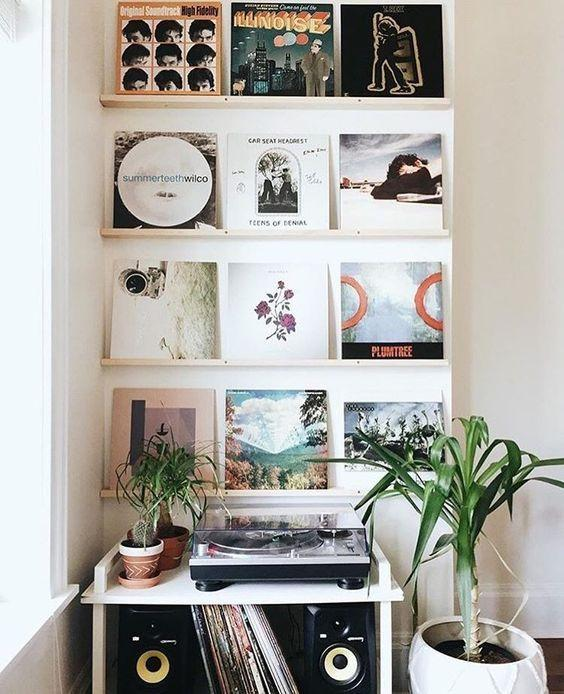 Vinyl record covers arranged in small wooden brackets on the wall.